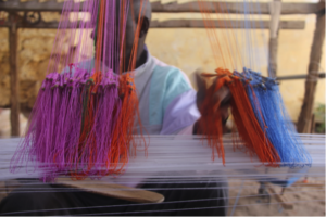 Assistant weaver helping weave Manjak textile